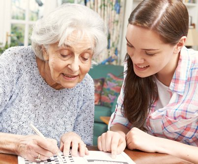 patient writing with her caregiver
