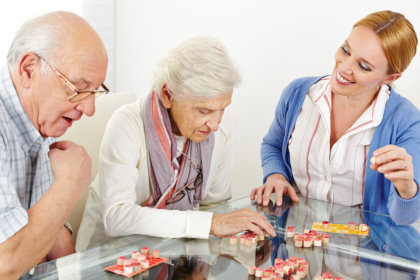 elderly people and caregiver playing board games